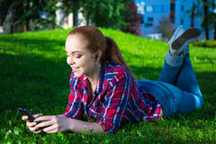 Música de mentira y que escucha del adolescente sonriente con el teléfono elegante Foto de archivo libre de regalías