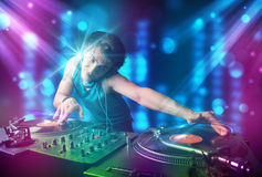 Música de mezcla de DJ en un club con las luces azules y púrpuras Imagen de archivo