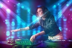 Música de mistura da menina do DJ em um clube com luzes azuis e roxas Foto de Stock
