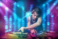 Música de mistura do DJ em um clube com luzes azuis e roxas Imagens de Stock Royalty Free