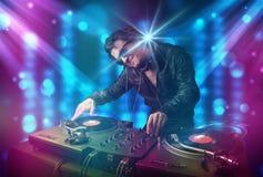Música de mistura do DJ em um clube com luzes azuis e roxas Imagens de Stock