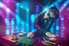 Música de mistura do DJ em um clube com luzes azuis e roxas Imagem de Stock
