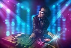 Música de mistura do DJ em um clube com luzes azuis e roxas Foto de Stock Royalty Free