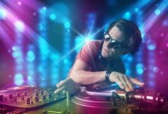 Música de mistura do DJ em um clube com luzes azuis e roxas Fotografia de Stock
