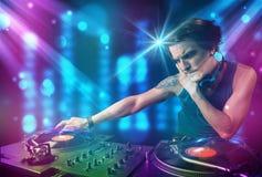 Música de mistura do DJ em um clube com luzes azuis e roxas Fotos de Stock