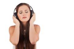 Música del disfrute de la mujer joven en auriculares Imagen de archivo