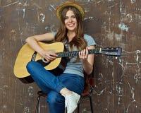 Música del juego de la mujer joven en la guitarra acústica Imagenes de archivo
