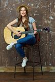 Música del juego de la mujer joven en la guitarra acústica Fotos de archivo libres de regalías