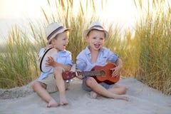 Música del juego de niños junto en la playa foto de archivo