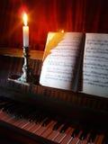 Música del piano y de hoja en la iluminación de la vela Foto de archivo