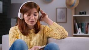 Música do canto da menina, mulher caucasiano nova que relaxa, sentando-se no sofá e escutando a música Lazer e abrandamento em video estoque