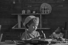 Música do canto do rapaz pequeno ao martelar pregos no bloco de madeira Criança pequena que senta-se na tabela de funcionamento n foto de stock royalty free