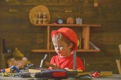 Música do canto do rapaz pequeno ao martelar pregos no bloco de madeira Criança pequena que senta-se na tabela de funcionamento n imagem de stock royalty free