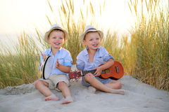 Música do jogo de crianças junto na praia Foto de Stock Royalty Free