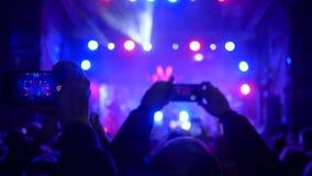 Música en directo, muchedumbre de fans con el teléfono celular en manos en el concierto de rock en la iluminación del proyector almacen de metraje de vídeo
