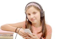 Música inalámbrica que escucha de la muchacha con los auriculares del teléfono elegante o Fotos de archivo libres de regalías