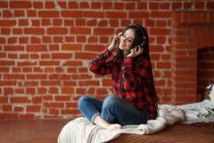 Música inalámbrica que escucha de la mujer con los auriculares de un teléfono elegante en casa Imagen de archivo libre de regalías