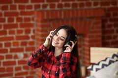 Música inalámbrica que escucha de la mujer con los auriculares de un teléfono elegante en casa Imágenes de archivo libres de regalías