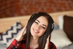 Música inalámbrica que escucha de la mujer con los auriculares de un teléfono elegante en casa Foto de archivo libre de regalías
