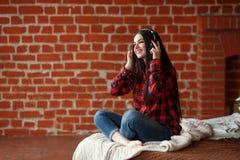Música inalámbrica que escucha de la mujer con los auriculares de un teléfono elegante en casa Imagenes de archivo
