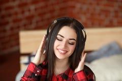 Música inalámbrica que escucha de la mujer con los auriculares de un teléfono elegante en casa Foto de archivo