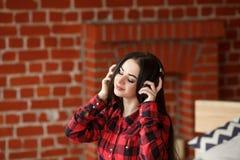 Música inalámbrica que escucha de la mujer con los auriculares de un teléfono elegante en casa Fotografía de archivo libre de regalías