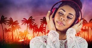 Música listenning da mulher ocasional feliz com os fones de ouvido na frente do fundo das árvores do plam Foto de Stock