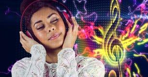 Música listenning de la mujer casual feliz con los auriculares delante del fondo de la nota musical Imagen de archivo