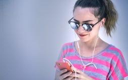 Música moderna nova do aquecimento da mulher com seu telefone celular imagem de stock royalty free