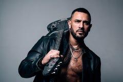 Música para o conceito do DJ Homem brutal à moda com uma barba, uma guitarra da terra arrendada da tatuagem Olhar 'sexy' de um mo imagem de stock