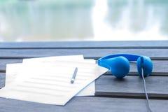 música que compone con el auricular azul y en el escritorio de madera Fotografía de archivo