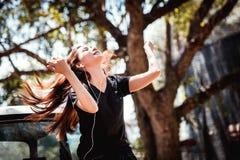 Música que escucha adolescente de la juventud asiática feliz en el teléfono móvil Imágenes de archivo libres de regalías