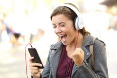 Música que escucha adolescente emocionada en un teléfono Foto de archivo