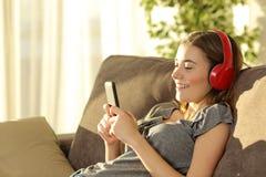 Música que escucha adolescente en línea con un teléfono elegante Fotos de archivo libres de regalías