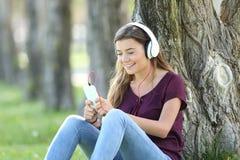 Música que escucha adolescente en línea en un parque Imagenes de archivo