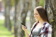 Música que escucha adolescente feliz en línea al aire libre Imágenes de archivo libres de regalías