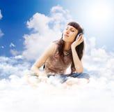 Música que escucha adolescente hermosa en las nubes Imagenes de archivo