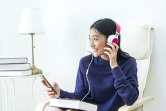 Música que escucha adolescente hermosa en smartphone con el auricular Imagenes de archivo