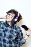 Música que escucha adolescente joven de la mujer con los auriculares Fotos de archivo