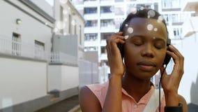 Música que escucha afroamericana hermosa con el auricular en la calle en la ciudad almacen de video