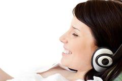 Música que escucha alegre de la mujer joven con los auriculares Foto de archivo