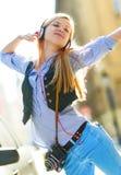Música que escucha alegre de la mujer joven en auriculares en la ciudad Foto de archivo libre de regalías