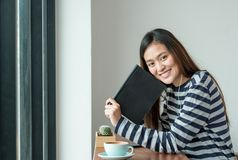Música que escucha asiática del libro de lectura de la mujer con la sentada móvil en Fotos de archivo