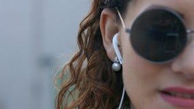 Música que escucha atractiva de la señora joven en su teléfono en el cierre de la calle para arriba metrajes