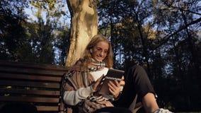 Música que escucha bonita de la mujer joven y tableta con mientras que se sienta en el banco en el parque verde almacen de video