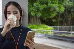 Música que escucha de consumición del café de la mujer con las auriculares del smartphone H Imagen de archivo libre de regalías