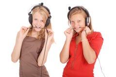 Música que escucha de dos adolescentes bonitos en sus auriculares Foto de archivo