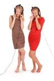 Música que escucha de dos adolescentes bonitos en sus auriculares Imagen de archivo libre de regalías