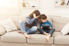 Música que escucha de dos niños en el sofá en casa Fotos de archivo