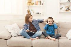 Música que escucha de dos niños en el sofá en casa Fotos de archivo libres de regalías